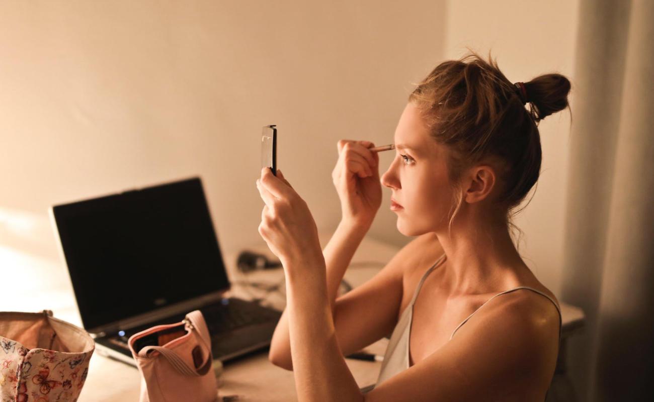 Doświetlona twarz kobiety robiącej makijaż